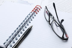 Pen, notebook, glasses and financial report Stock Images