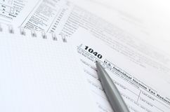 The pen and notebook is lies on the tax form 1040 U.S. Individua. L Income Tax Return. The time to pay taxes Stock Photo