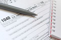 The pen and notebook is lies on the tax form 1040 U.S. Individua royalty free stock images