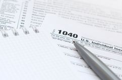 The pen and notebook is lies on the tax form 1040 U.S. Individua. L Income Tax Return. The time to pay taxes Royalty Free Stock Photos