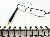Pen Notebook och exponeringsglas i sammansättning Arkivbild