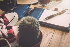 Pen and notebook with personal accessory on table. Royalty Free Stock Photos