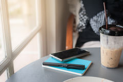 Pen, notebook, and smartphone on table Stock Photography