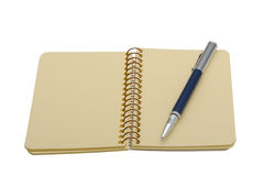 Pen and a notebook on a spiral with a yellow paper Stock Image