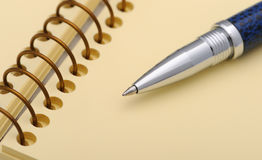 Pen and a notebook on a spiral with a yellow paper Stock Images