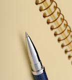 Pen and a notebook on a spiral with a yellow paper Stock Photography