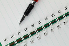 A pen and a notebook take notes. A pen is locate on a notebook takes notes royalty free stock photo