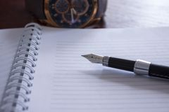 Pen and notebook with a watch in the background, visual identity for business people stock image