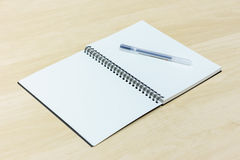 Pen and notebook. On wooden desk royalty free stock photos