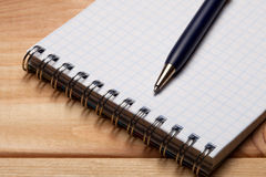 Pen and notebook on wooden table. Royalty Free Stock Images