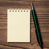 Pen and notebook on wooden table. Royalty Free Stock Photo