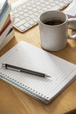 Pen with notebook on working table Stock Photography
