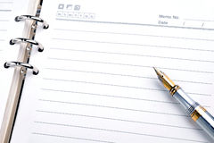 Pen and notepad. A gold nibbed pen on a Blank notepad Stock Photo