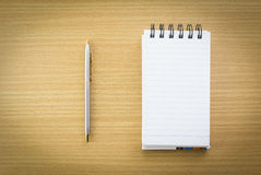 Pen and notepad with blank page. Pen and open notepad with blank page on wood table Stock Photo