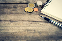 Pen, notepad and coins on wooden background Stock Photos