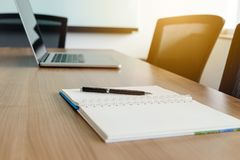 Pen on notepad and laptop and for agenda kept on table in empty corporate conference room. Selected focus on pen and notepad royalty free stock image