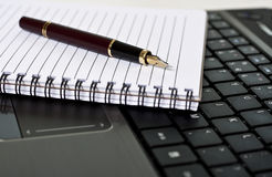 Pen, notepad and laptop on the desk Royalty Free Stock Photos