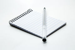 A pen and notepad with a plain white background.  Royalty Free Stock Photography