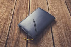 Pen on notepad on vintage wooden table royalty free stock photography