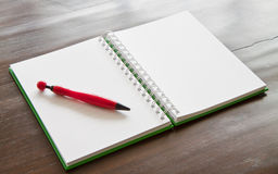 Pen and notepad on wooden table Royalty Free Stock Images