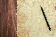 Pen and old aged paper on wood. For background stock photos