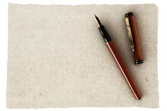 Pen and Old Paper. Elegant fountain pen over an old empty piece of parchment stock photography