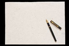 Pen and old paper. Isolated on black background Royalty Free Stock Photo