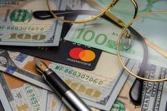 Pen, oogglazen en grafieken de glazen en een Mastercard-kaart zijn op dollars Cheboksary, Rusland, 11/25/2018 stock foto