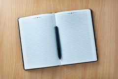 Pen on an open agenda or notebook with blank pages Royalty Free Stock Photos