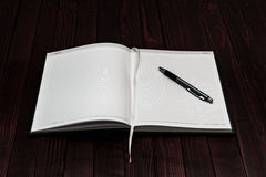 A Pen on Open Blank Notebook on Wooden Background. Business Concept. Selective Focus Royalty Free Stock Image
