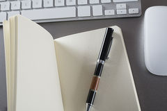 Pen on an open notebook with keyboard and mouse Stock Images