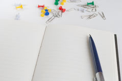 Pen on the  open notebook for writing text. On a background paper clip Stock Image