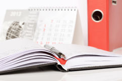Pen on an opened notebook and a calendar. Office supplies on the table Royalty Free Stock Images