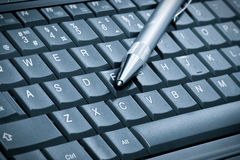 Pen over laptop keyboard Stock Photography