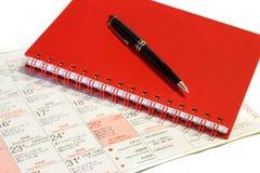 Pen over notebook on Christmas calendar. Royalty Free Stock Photos