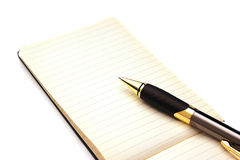 Pen and paper. An old yellowed note pad is opened to a blank lined page. A pen is resting on the notebook and the pages are slightly yellowed Royalty Free Stock Photos