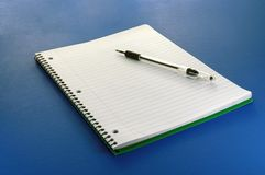 Pen & Paper. A notebook and pen close-up on a blue background stock image