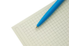 Pen and paper. Blue pen lying on the white sheet into the cell Stock Image