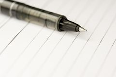 Pen and paper. A pen on a blank paper ready to write Royalty Free Stock Photo
