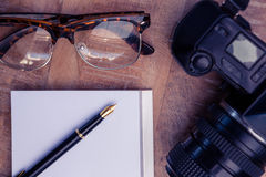 Pen on paper by camera and eye glasses at table Stock Image