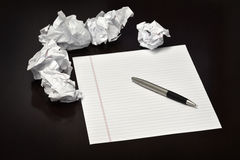 Pen and Paper on Desk with Discarded Trashed Ideas. Pen and paper on a desk with discarded trashed ideas written ouit Stock Image