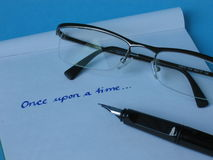 Pen Paper Glasses. A fountain pen on written paper with glasses Royalty Free Stock Image