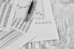 Pen on paper with the price quotes and charts stock photos