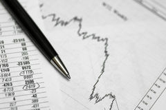 Pen on paper with the price quotes and charts stock image