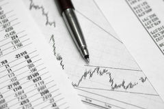 Pen on paper with the price quotes and charts royalty free stock image