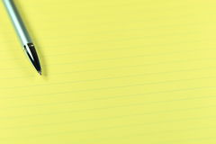 Pen and Paper. Single silver pen resting on yellow lined paper.  Shallow depth of field, focused on pen tip Royalty Free Stock Image