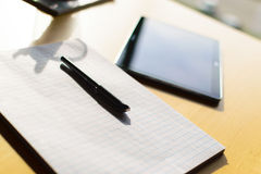 Pen, paper and tablet on table Royalty Free Stock Photo