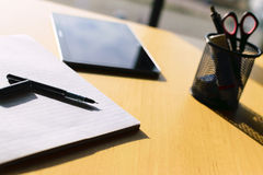 Pen, paper and tablet on table. At big wiindow. Shadows falling from pen cannister Stock Photography