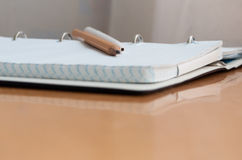Pen, pencil, book and notebook lying on the desk. Written on a yellow wooden table lay a pen notebook and pencil book Stock Photos