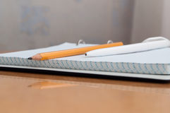 Pen, pencil, book and notebook lying on the desk. Written on a yellow wooden table lay a pen notebook and pencil book Royalty Free Stock Image